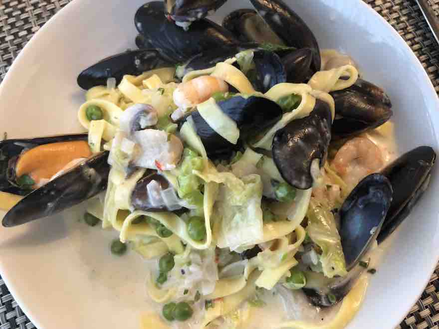 mussels and prawns with pasta and a cream sauce in a dish