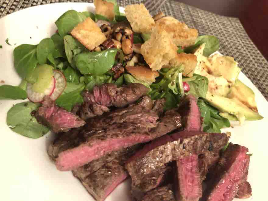 rump steak sliced on a white plate with lambs lettuce and homemade rosemary and garlic croutons