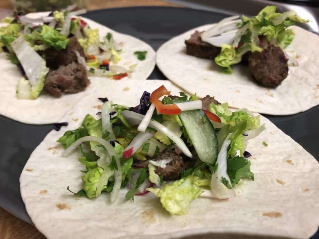 mini tortillas with mini kebabs and mixed salad on top