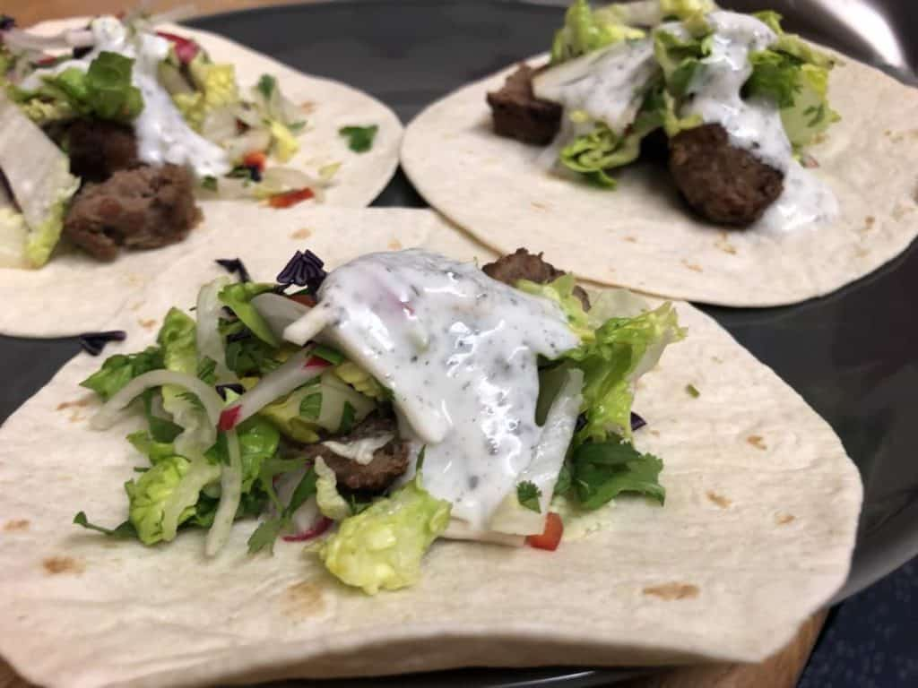 mini kebab with salad and then mint yogurt sauce on top